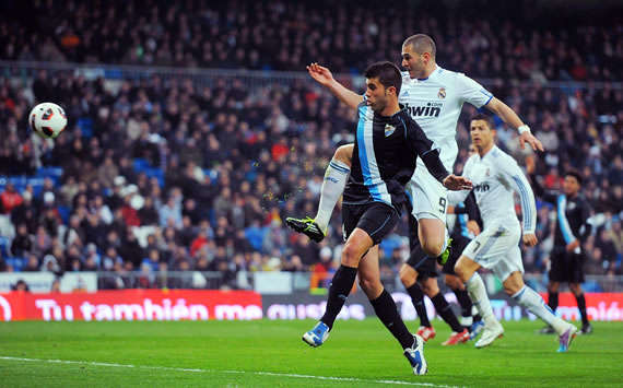 Karim Benzema tucks away Real Madrid's opener in the 7-0 mauling of Malaga (Getty Images)