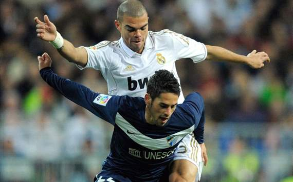 Isco (L) of Malaga is tackled by Pepe of Real Madrid