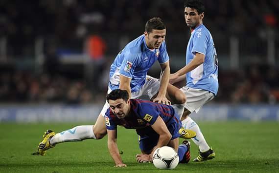 Xavi Hernández pelea con David Timor (L) y Xavier Annunziata en el Barcelona-Osasuna de Copa del Rey