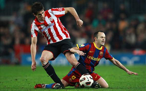 Javi Martinez battles with Andres Iniesta
