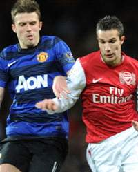 Robin van Persie of Arsenal takes on Michael Carrick