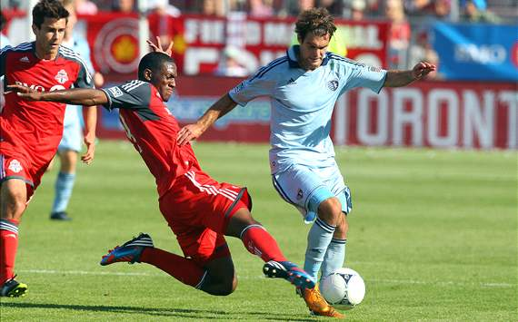 Toronto FC's Doneil Henry tackles Sporting Kansas City Graham Zusi