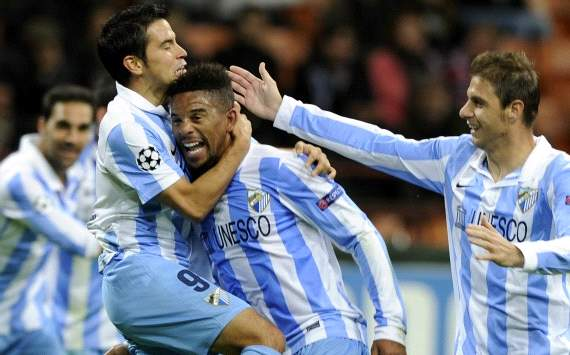 Malaga players celebrate Eliseu goal against Ac Milan