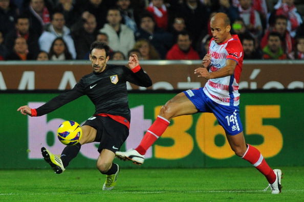 Atletico Madrid's midfielder Juanfran (L) vies for the ball Granada's midfielder Mikel Rico