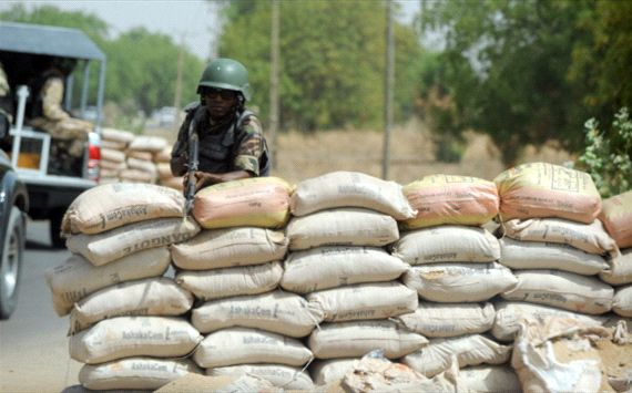 Soldier positions his rifle on sand bags on the road in northeastern Nigerian town of Maiduguri, Borno State